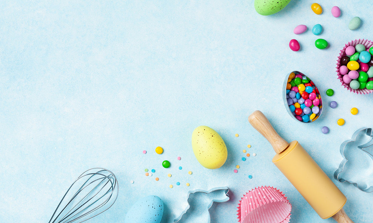 Easter eggs and cooking utensils on a light blue background