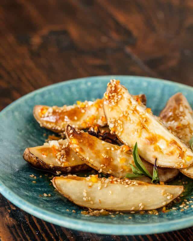 Asian roasted potato salad on a blue plate