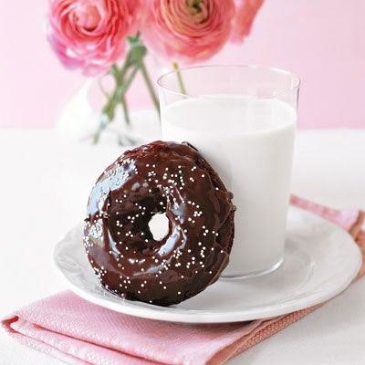 Double chocolate donuts leaning on a glass of milk