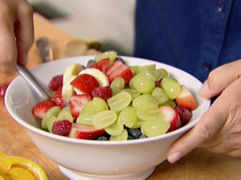 Hands scooping a fruit salad from a bowl