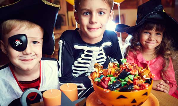 Three kids in costume over a bowl of candy