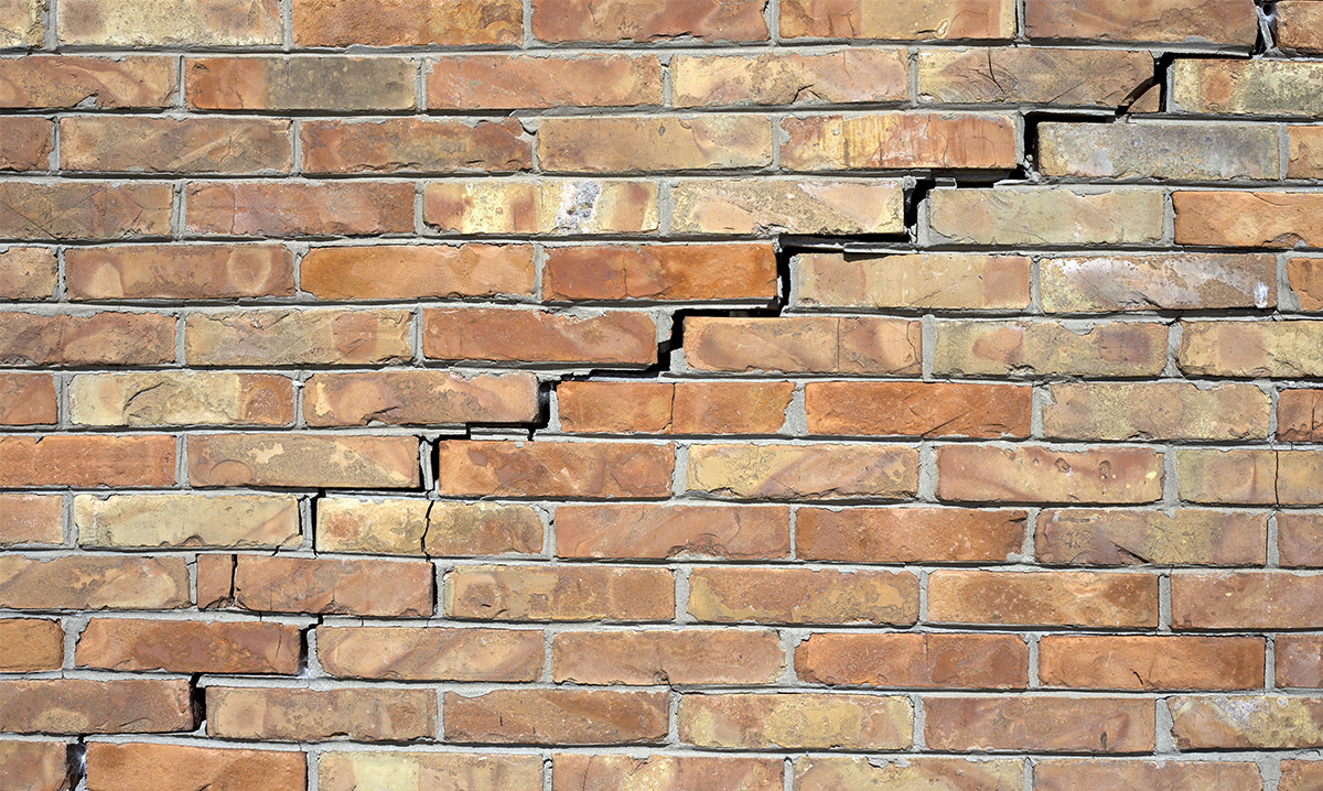 A brick wall with a crack in it