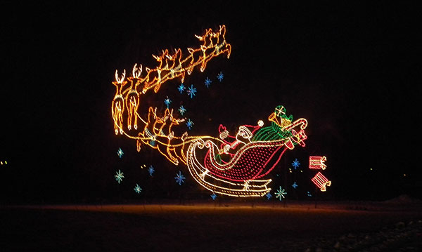 Light display of Santa and reindeer on a black background