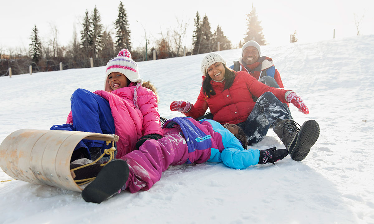 A family laughing while sledding