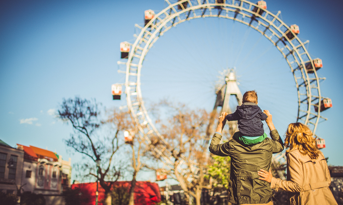 A kid sits on his dad's shoulders in front of a ferris wheel
