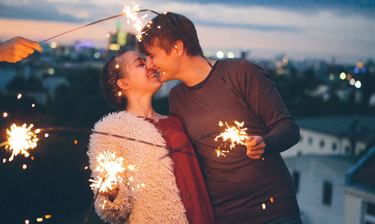 Teen boy and girl kissing while holding sparklers