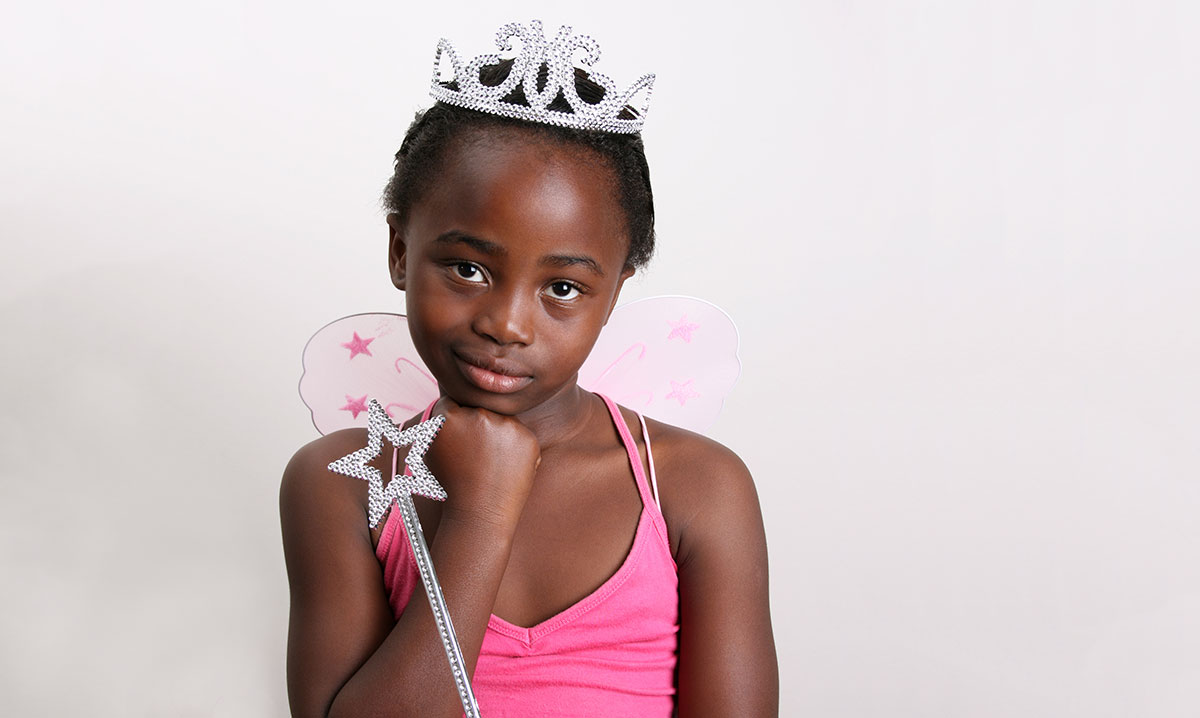 A little girl in a pink princess costume on a white background