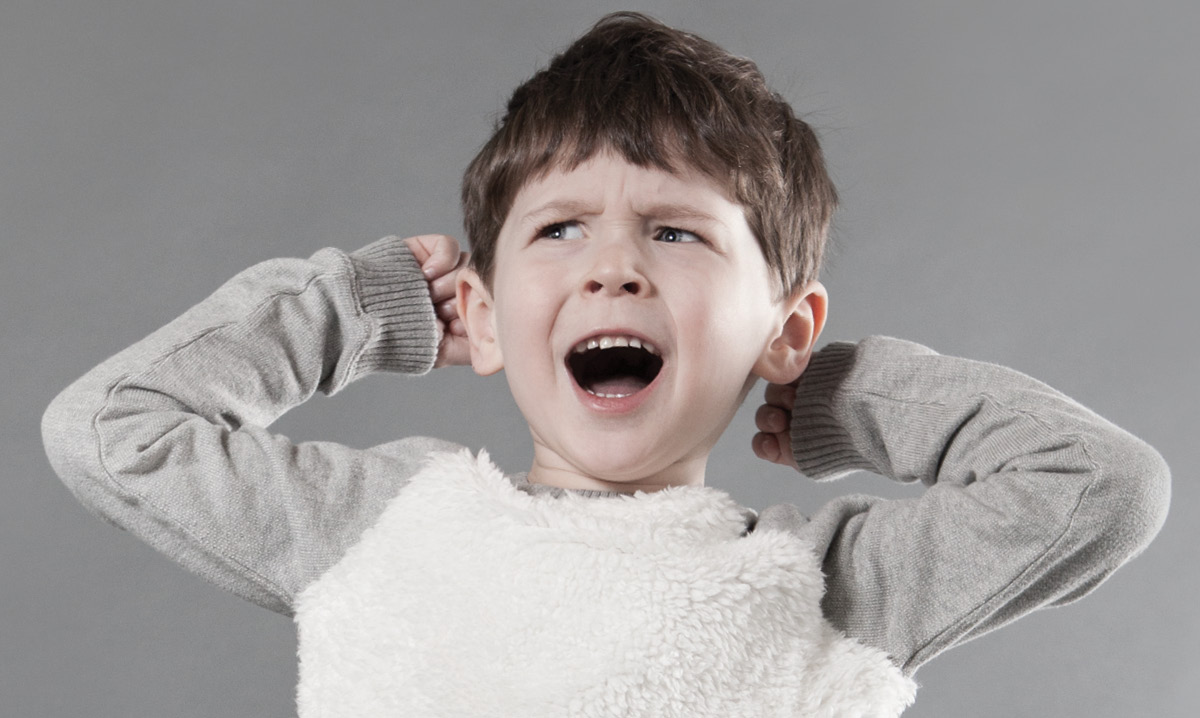 Child holding his ears while yelling on a gray background