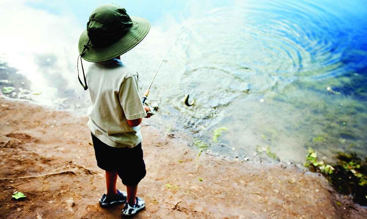 Little boy in shorts and a hat fishing from the shore