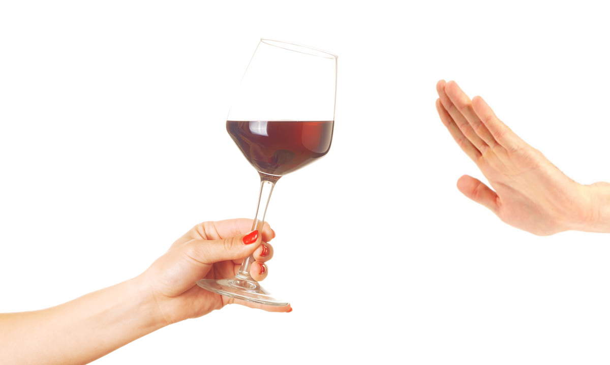 Hand waving away a glass of wine on a white background