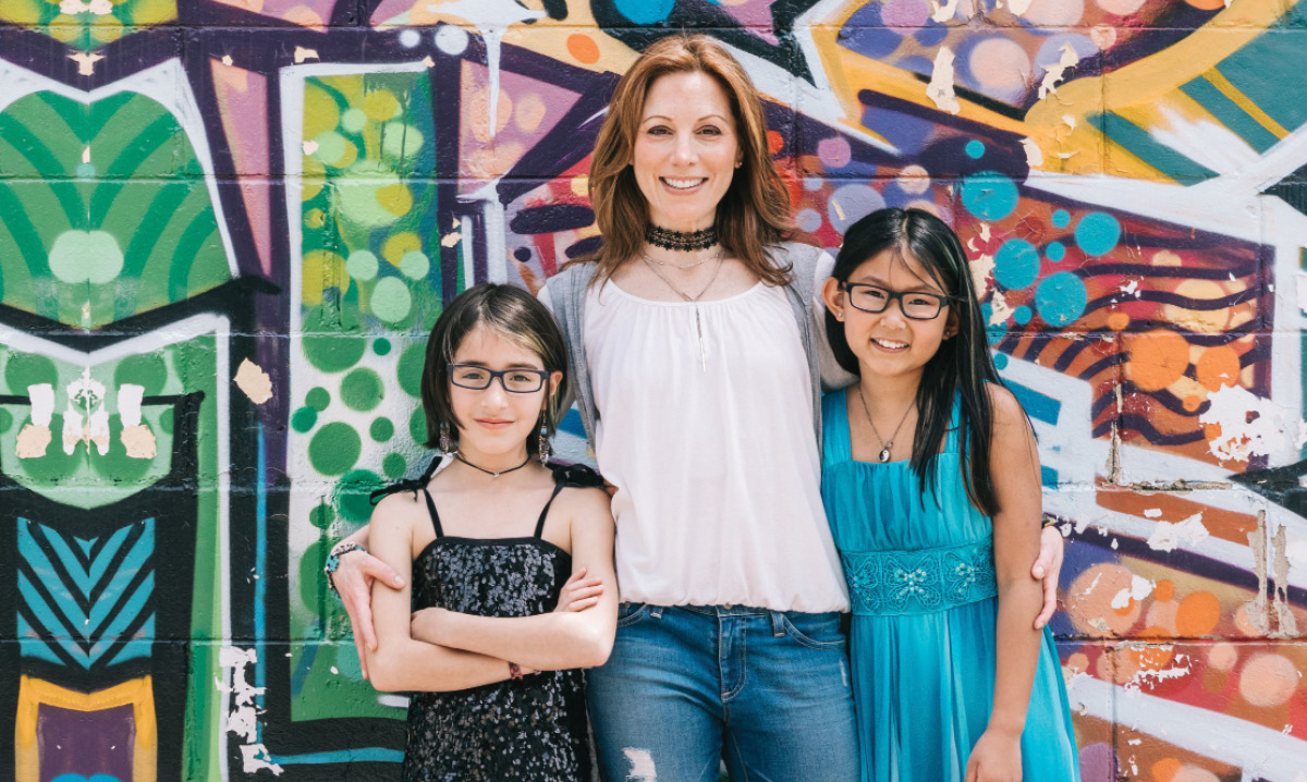 Robyn Coden and daughters Frankie and Jaye smile in front of a colorful wall