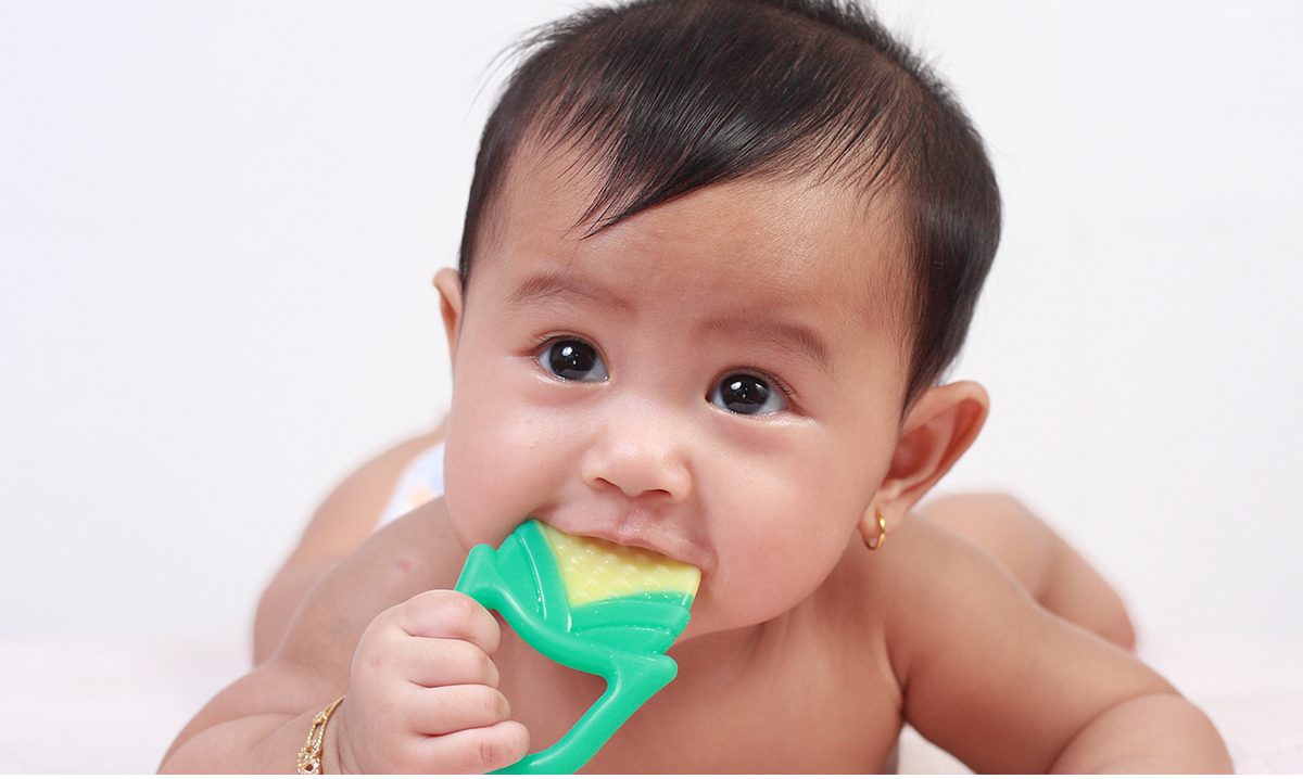 Baby chewing on a teething ring on a white background