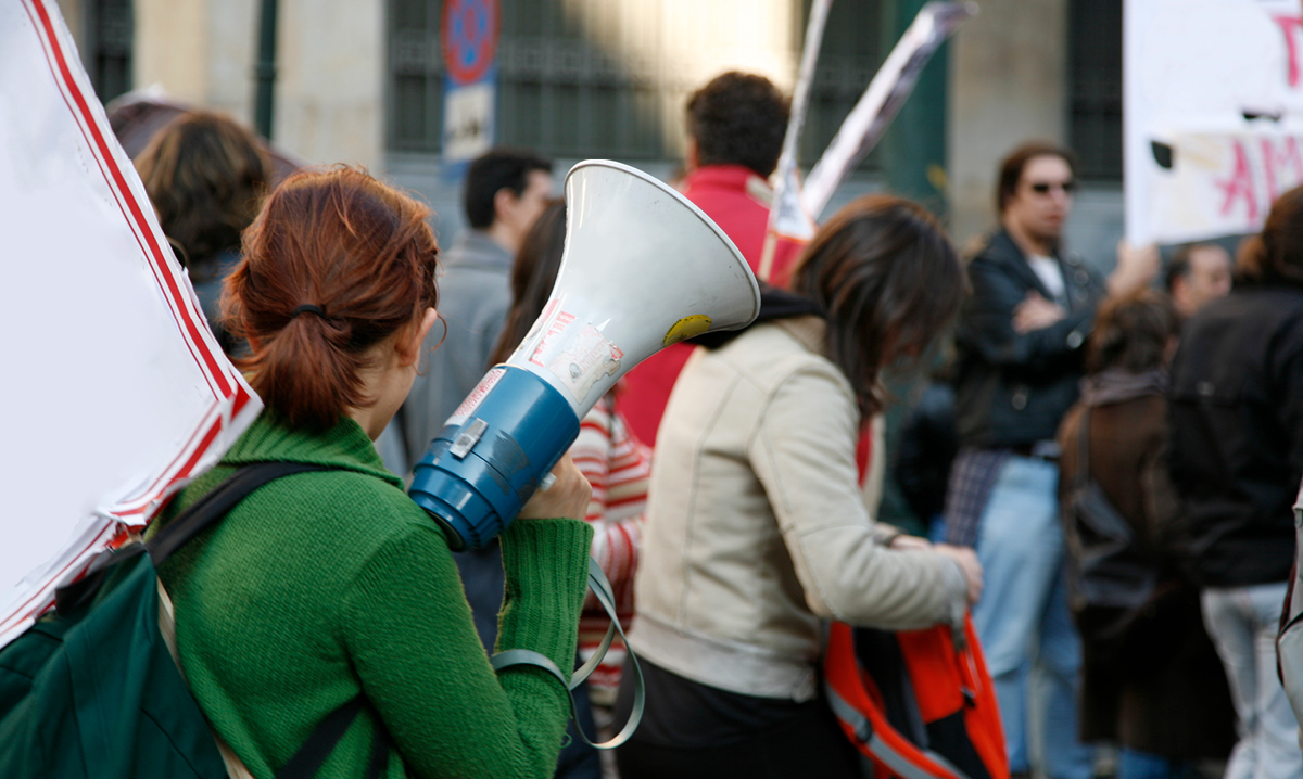 Woman standing with a megaphone at a protest