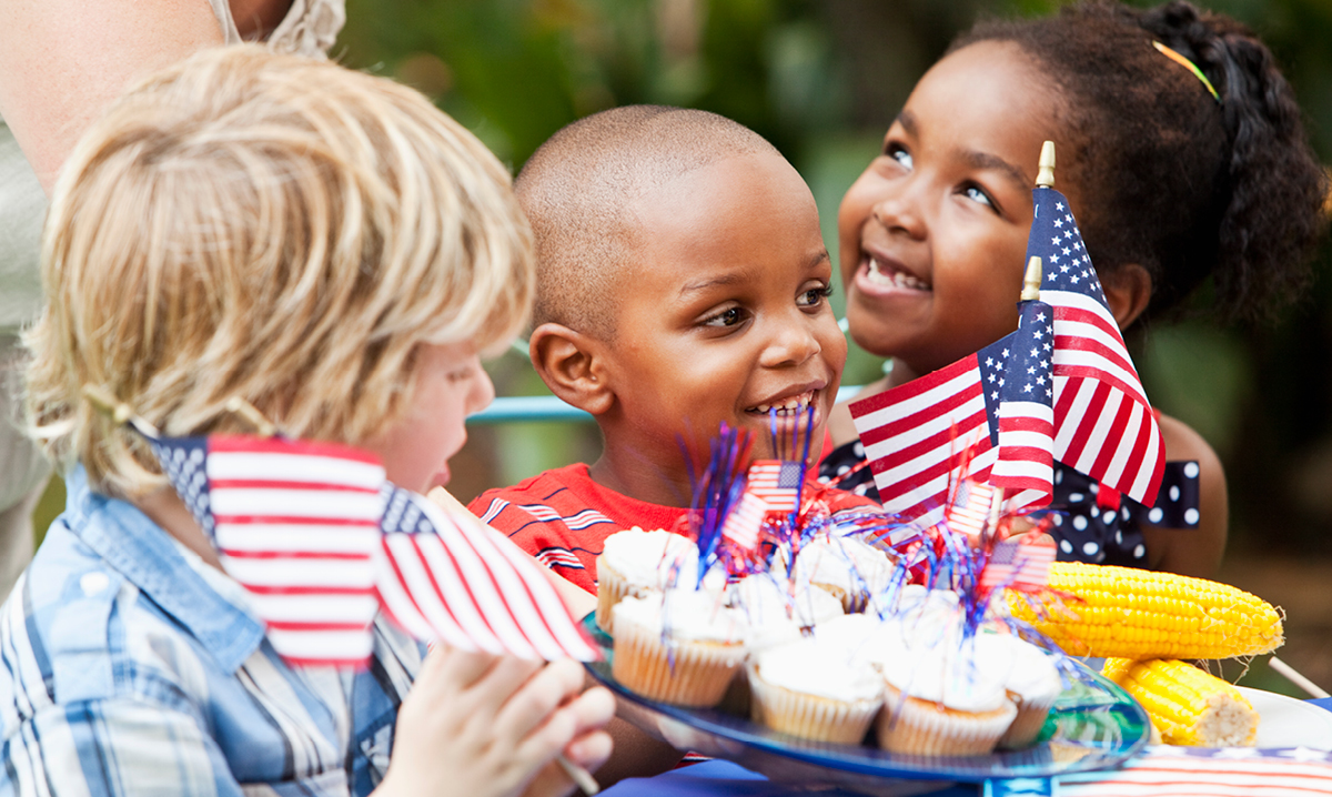 Three kids enjoy festive cupcakes at a Memorial Day weekend event