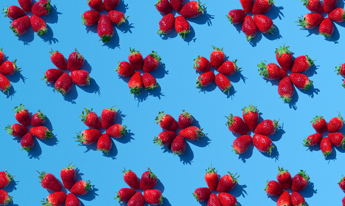 Strawberries stacked like flowers on a blue background