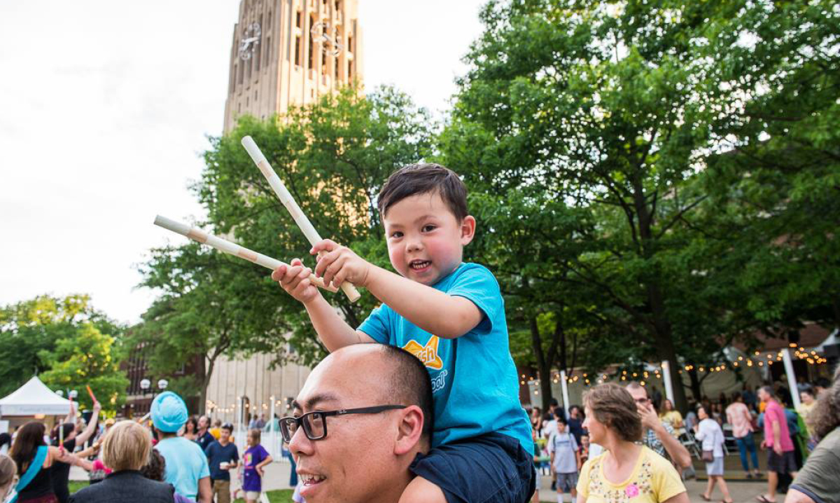 Little boy sitting on his dad's shoulders while holding sticks