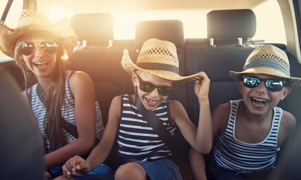 Three kids in backseat of car wearing straw hats and ready for summer fun