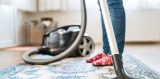 Woman in socks using a vacuum cleaner on the rug