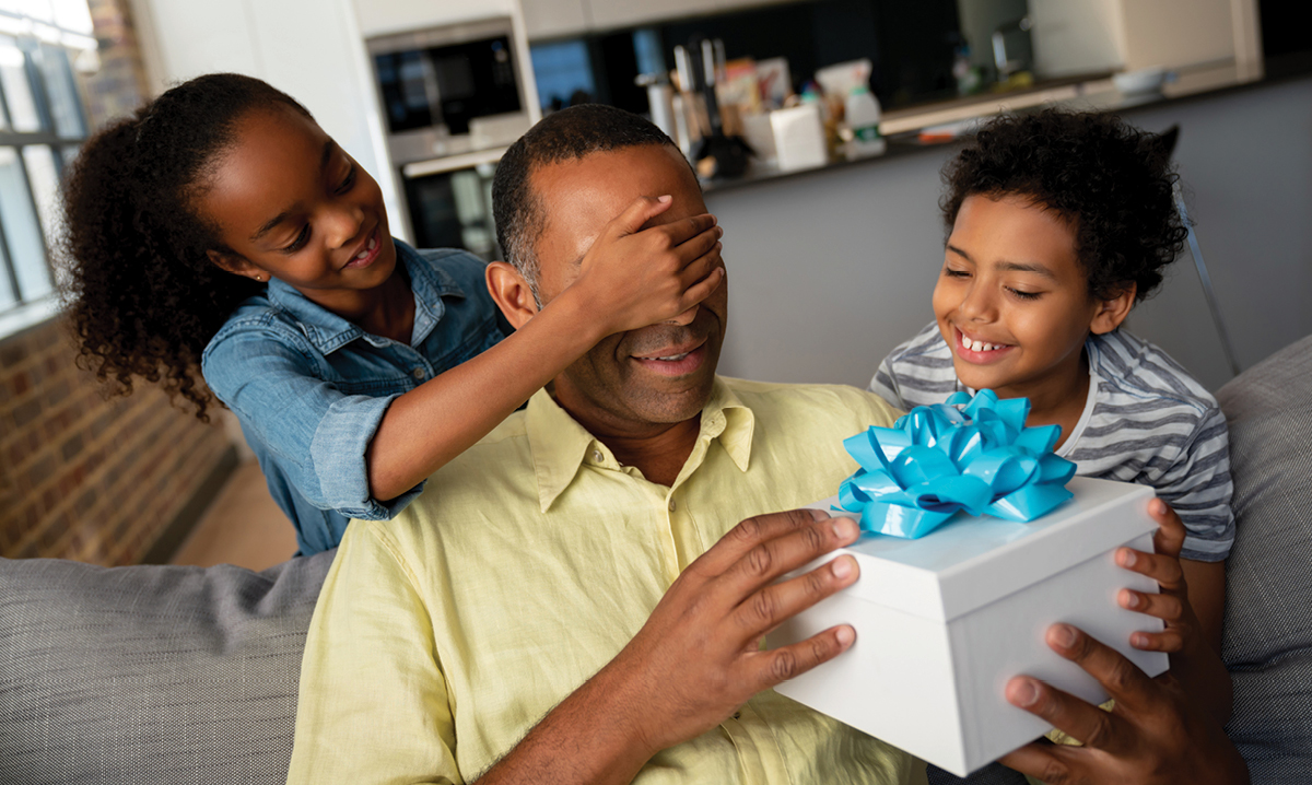 A boy and girl giving a gift to their dad