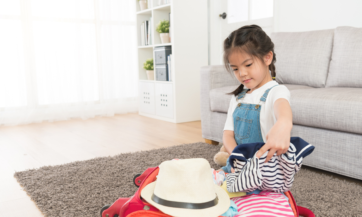 Little girl packing clothes for vacation