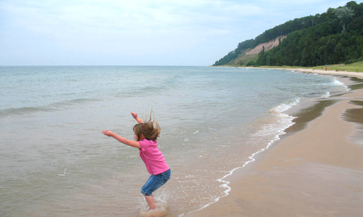 Girl jumping in water on a beach