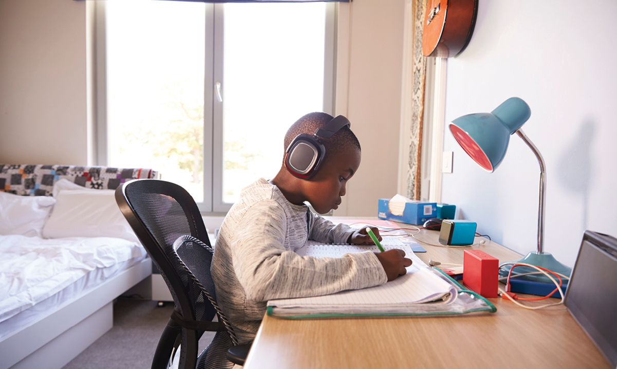 Child studying with headphones and music