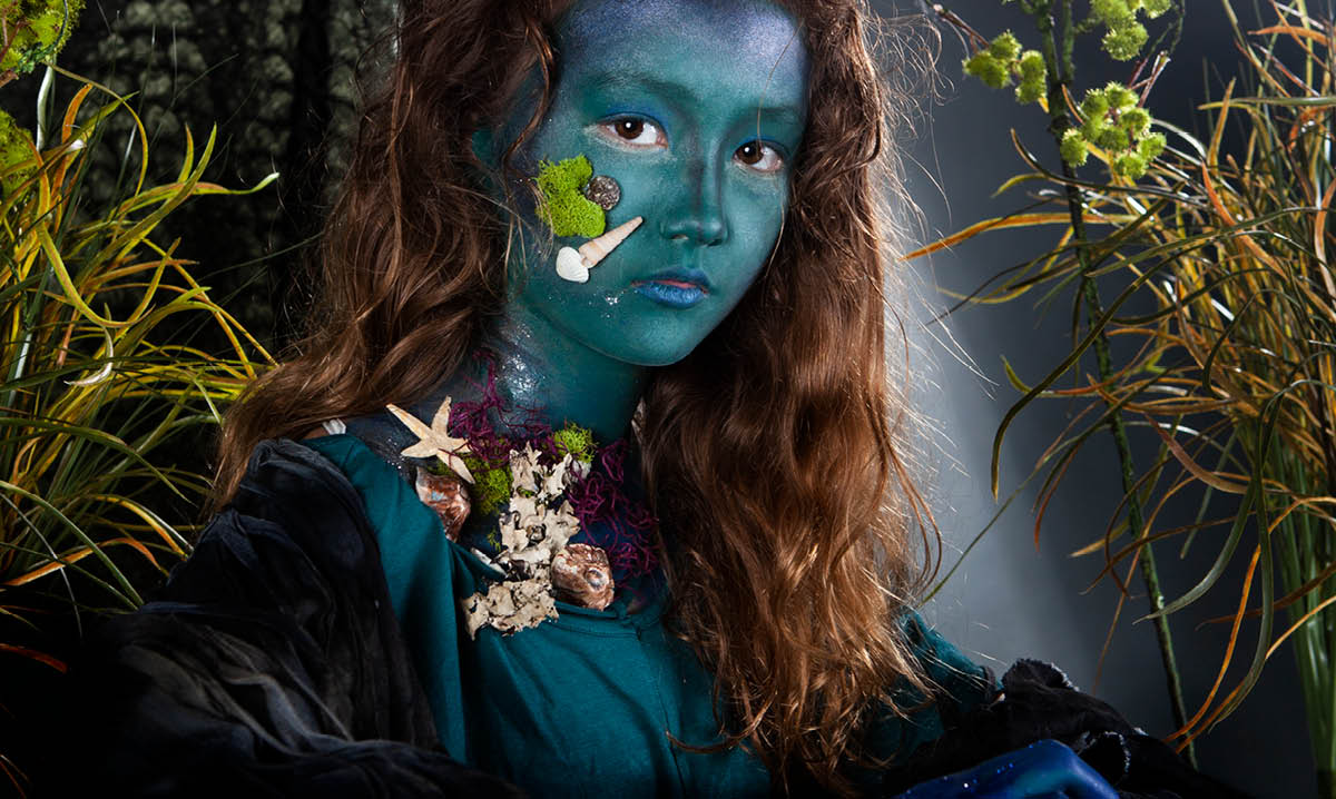 Girl in mermaid paint surrounded by leaves