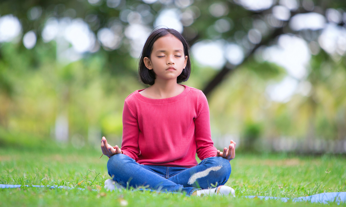Little girl in pink shirt sitting in the grass while meditating with her eyes closed a