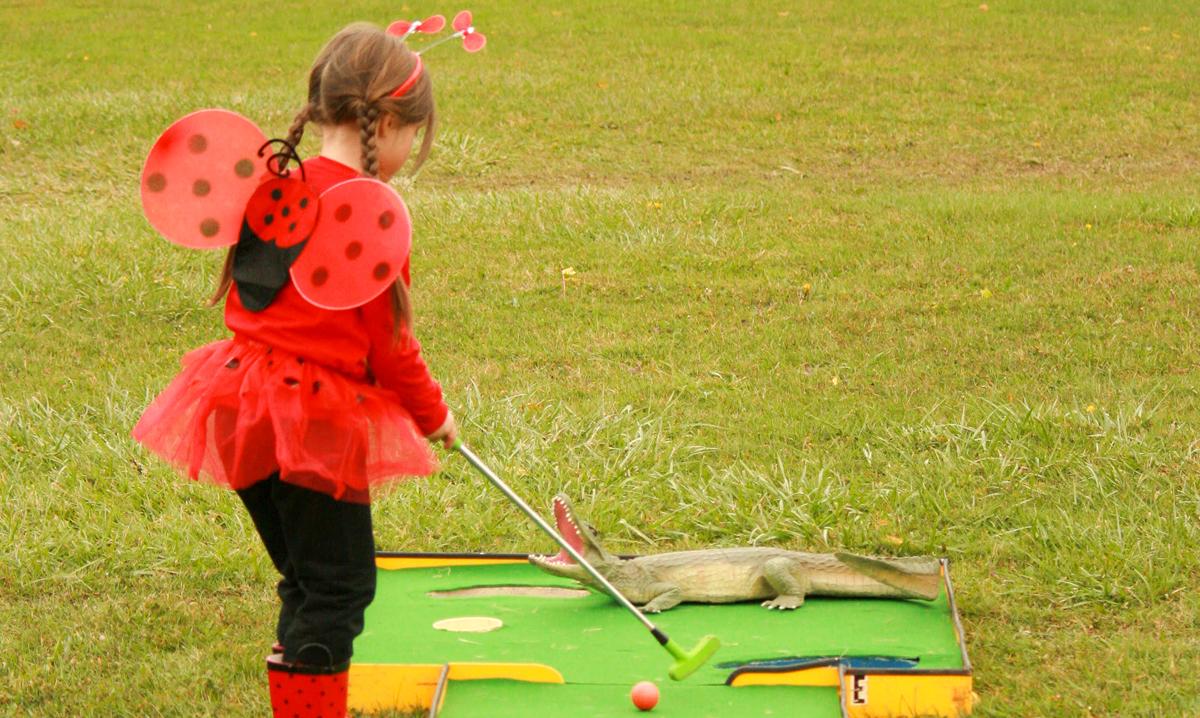 Little girl in lady bug costume playing mini golf