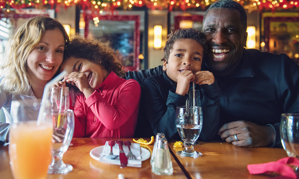 Family of four in a bar surrounded by drinks and plates