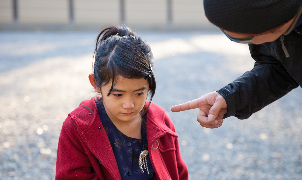 Little girl looks sad while man puts finger in her face