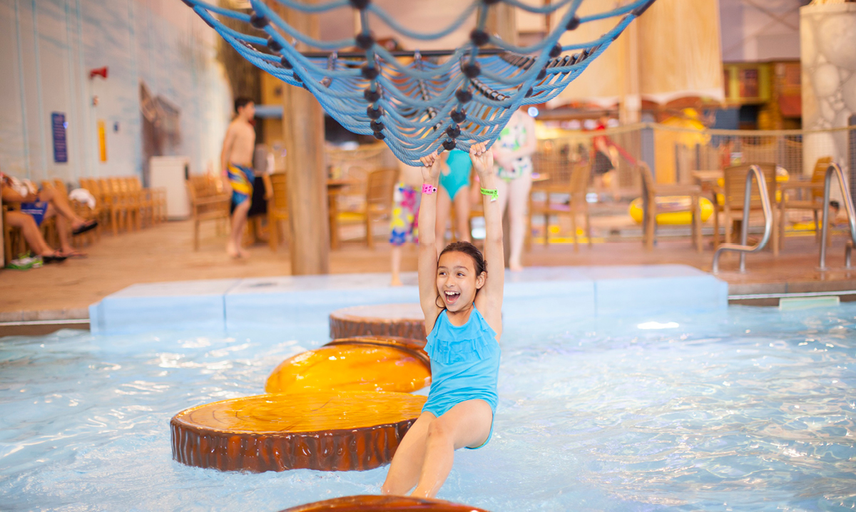 Girl hanging on net above a pool at an indoor waterpark