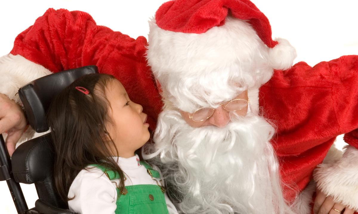 Girl in wheelchair whispering to Santa