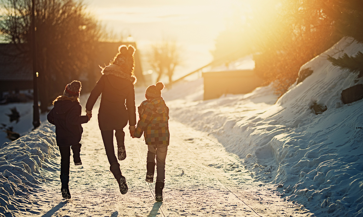 Two kids and a woman skipping through the snow