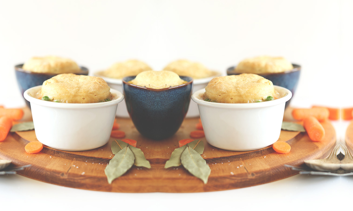 Vegan pot pies on a wooden cutting board on a white background