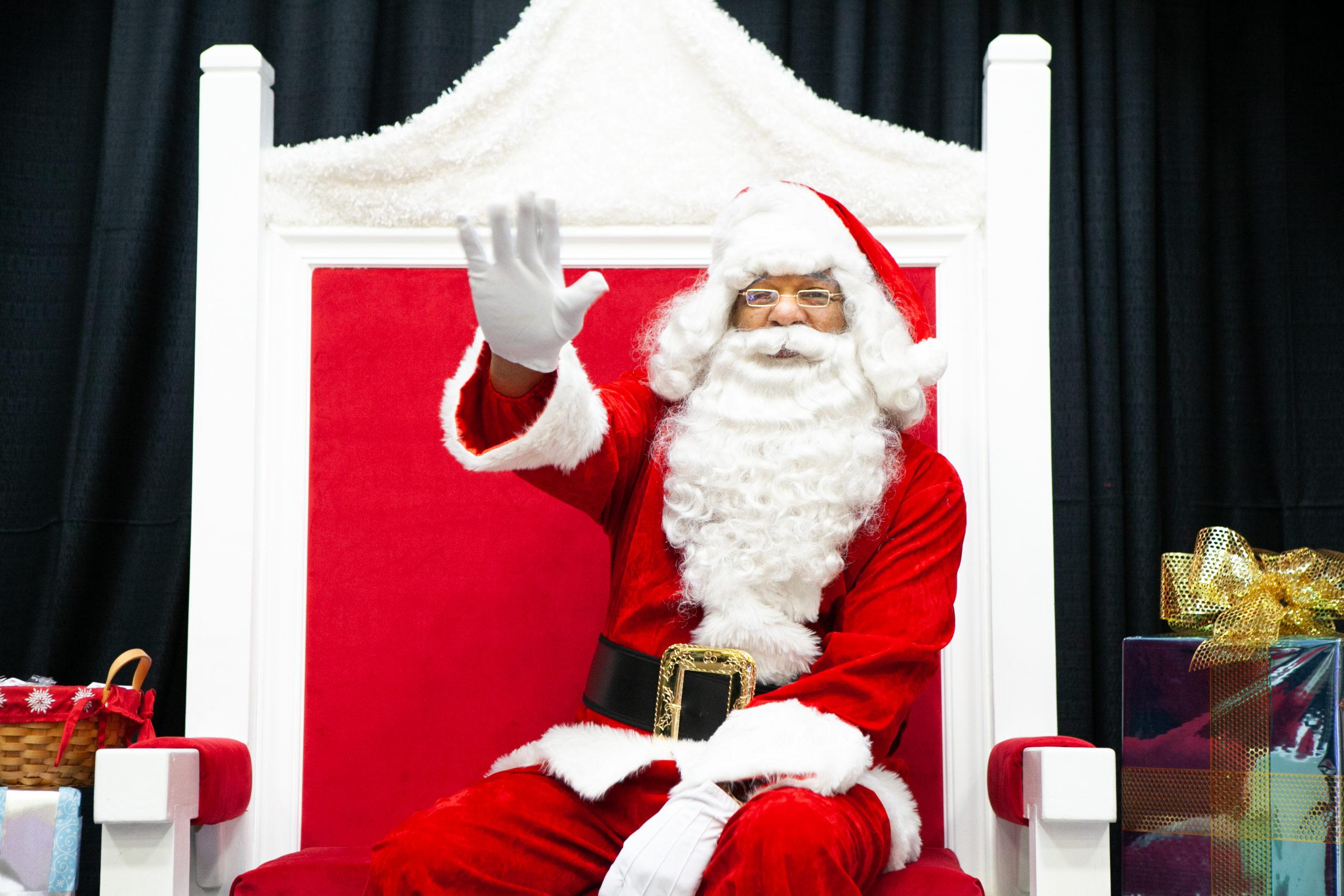 Santa waving from his chair at Black Santa event