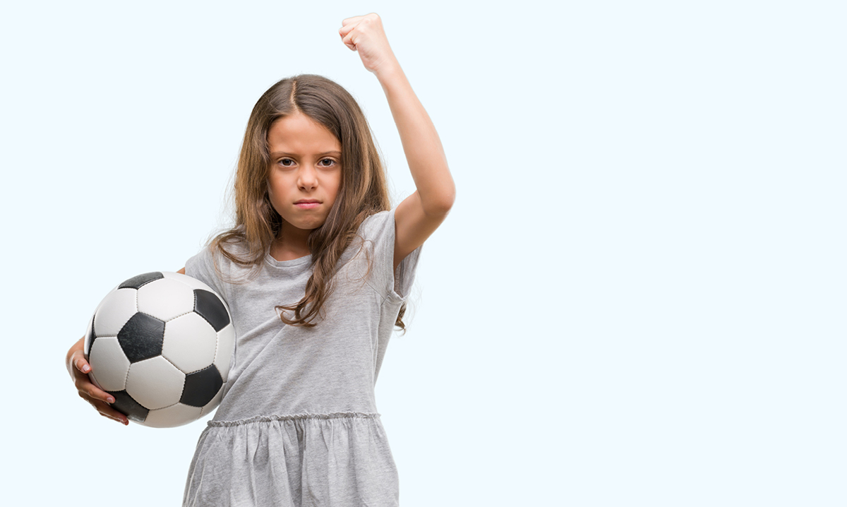 Girl holding soccer ball with fist raised