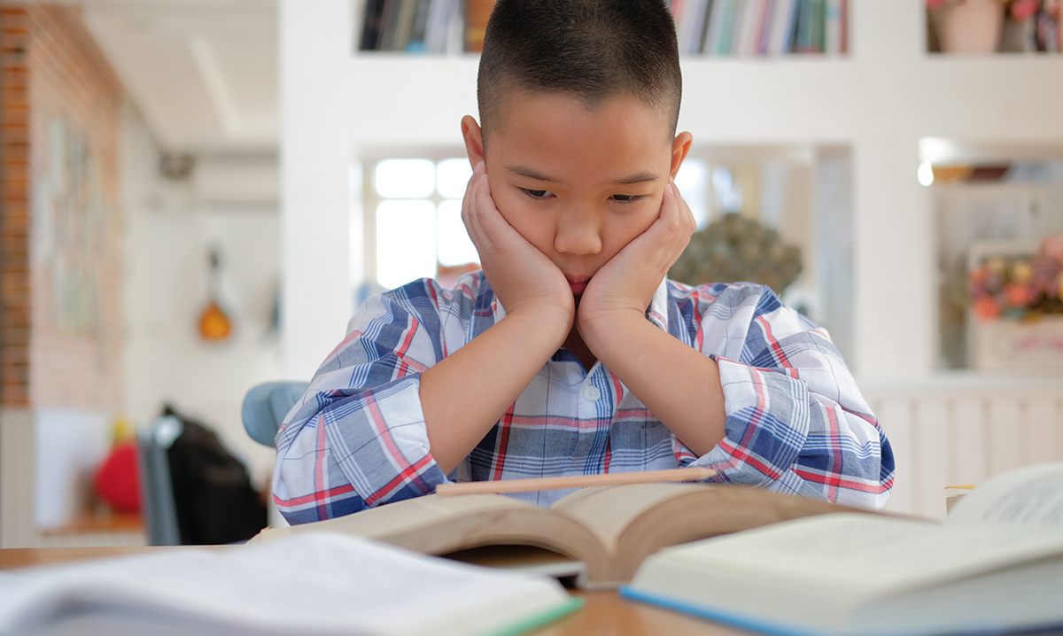 Young boy looks sad while reading