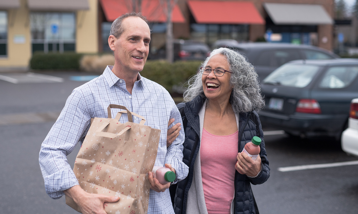 An elderly couple smiles while leaving store