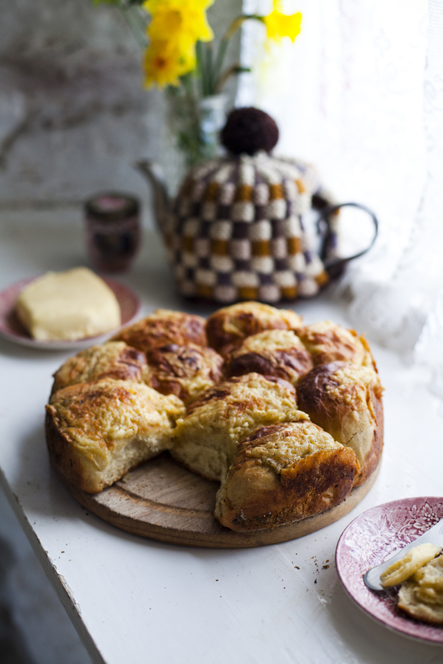 Potatoe Yeast Rolls on a plate in front of a brown flowerpot with yellow flowers