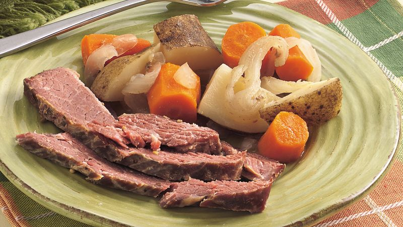 close-up of a slow-cooked corned beef dinner on a green plate