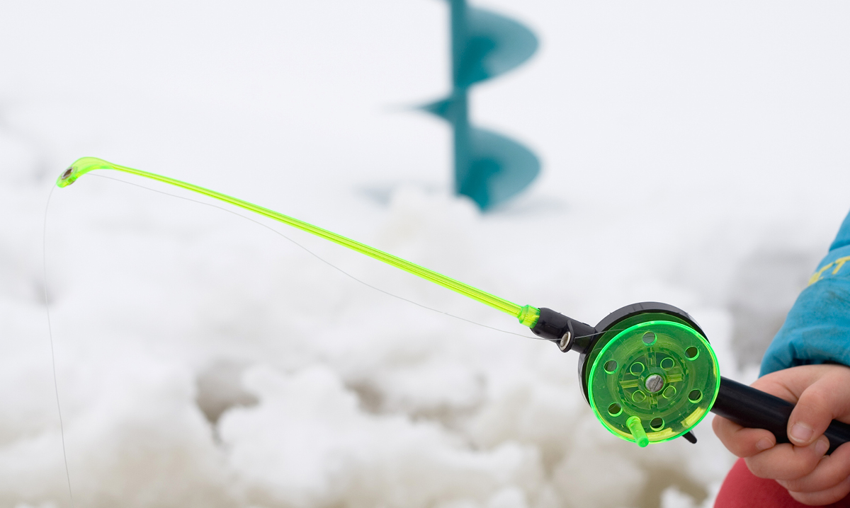 Green kids' fishing pole with snow in the background