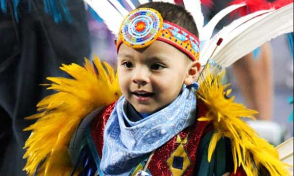 Young boy wearing Native American regalia