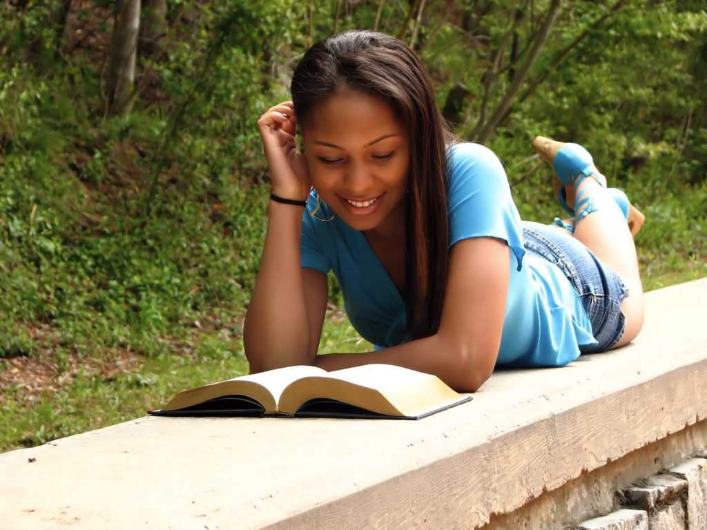 Teen reading and relaxing outside
