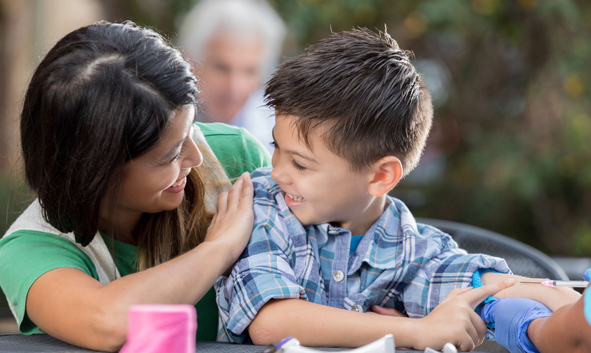 Mom reassures a young boy about to get a vaccination shot