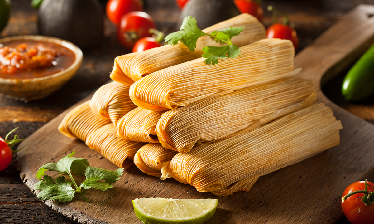 Nine tamales surrounded by tomatoes and lime