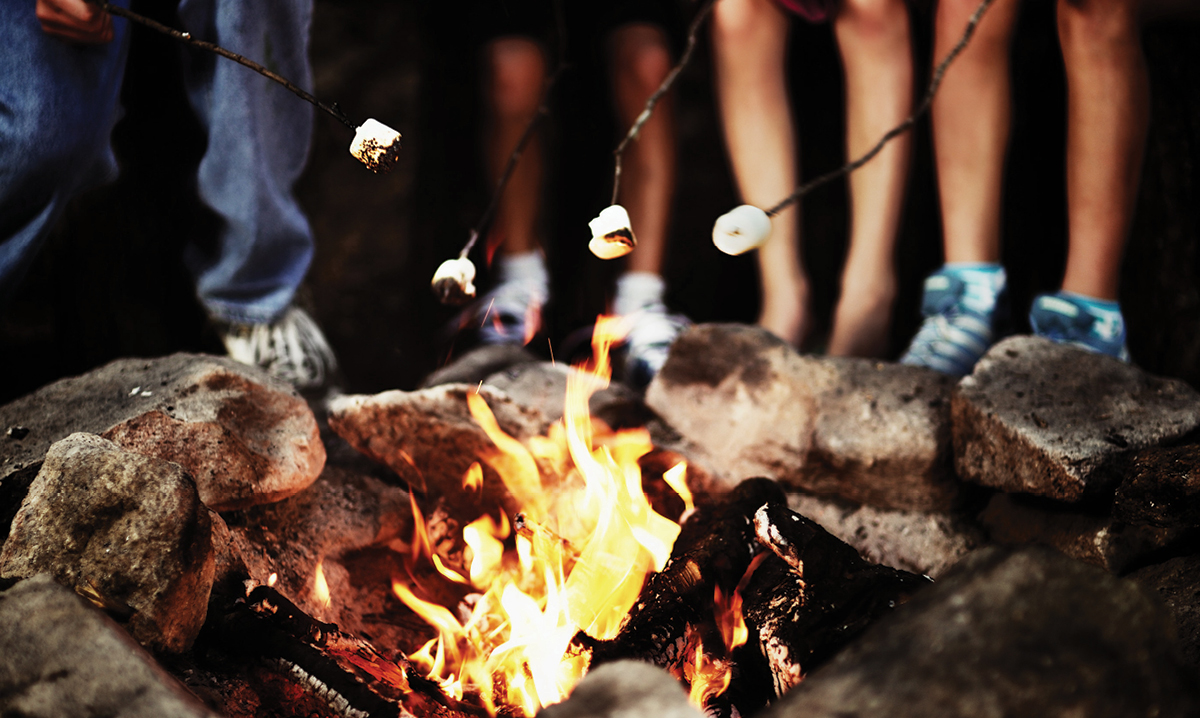Kids roasting marshmallows over a campfire