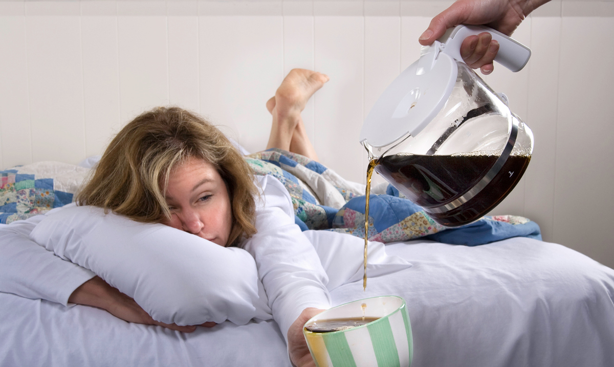 Mom in bed holding coffee cup that is being refilled
