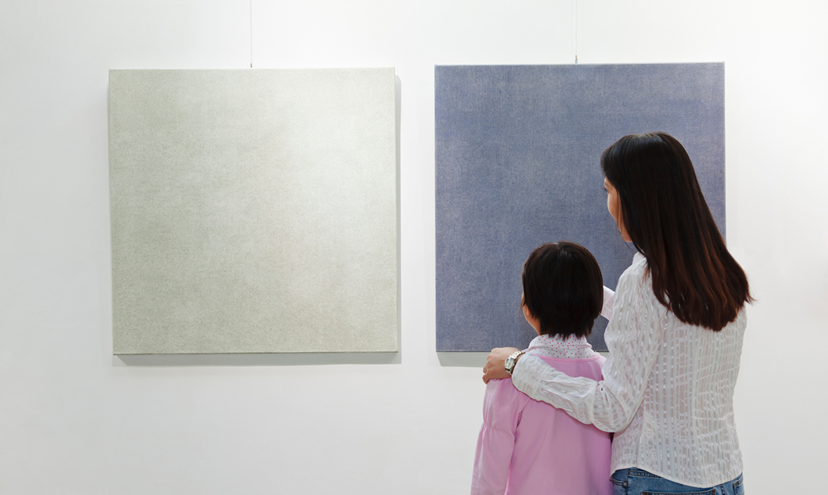 Woman and child staring at two pieces of art on a wall