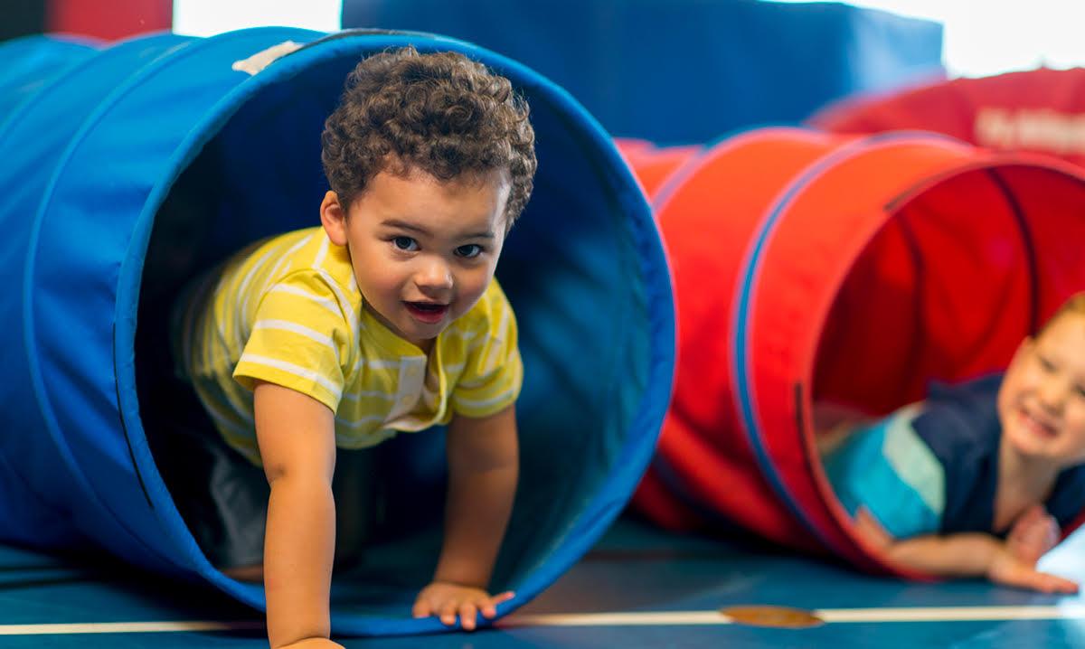 Toddler crawls through a blue play tube